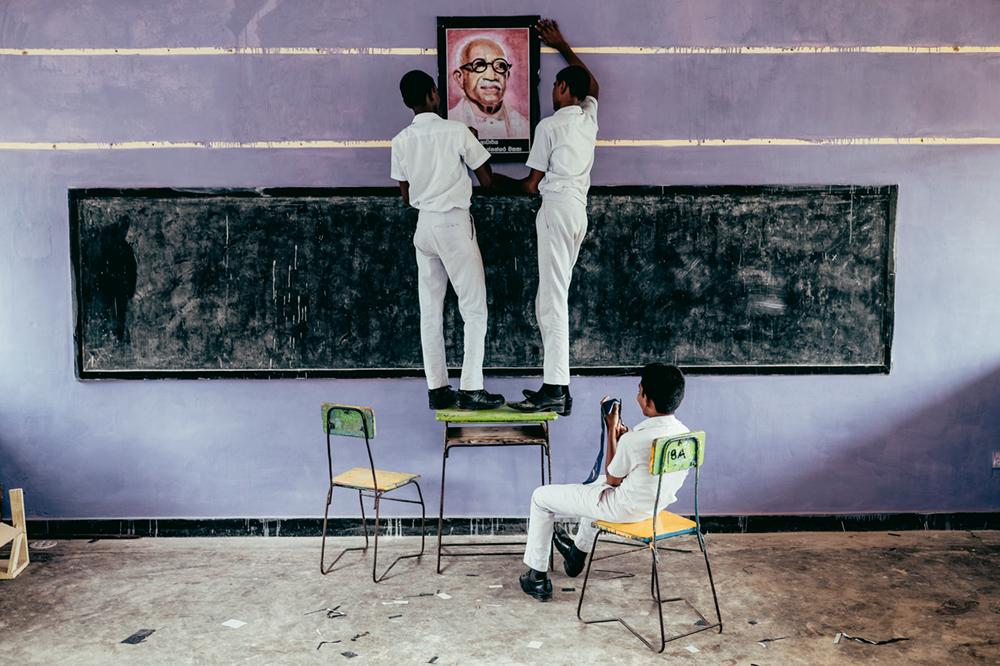 Teenager hängen während einer Mathematikstunde in einer Uferstadt im Süden Sri Lankas ein Bild des verstorbenen sri-lankischen Anwalts Kannangara auf  Photo © 2019 Pie Aerts. All rights reserved.