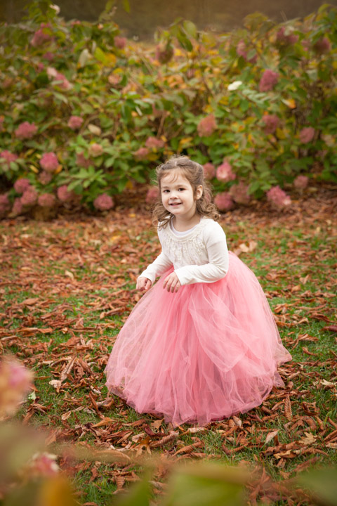 This girl was crazy over tutus, so we chose to put her in a floor length pink tutu, and place her amidst the hydrangea bushes. The framing of the branches  creates a feel that the viewer is catching a genuine moment while this girl is in her own world, dancing among the flower maze.