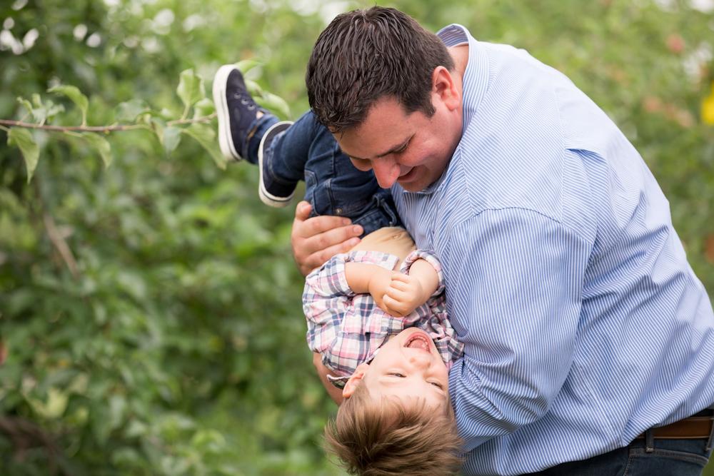 dad-son-kid-silly-tickling-spring-orchard.jpg