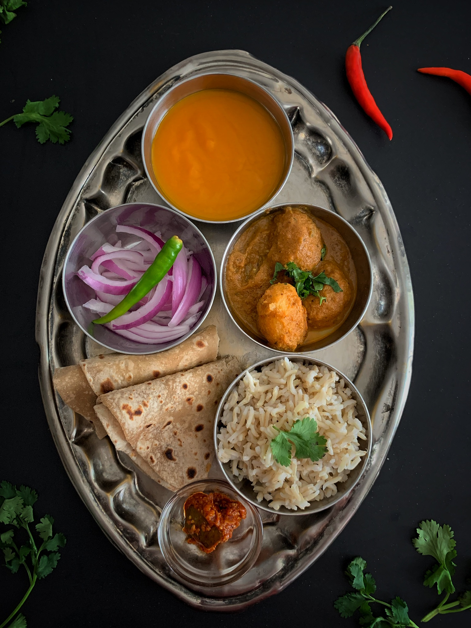 Indian Thali with Dum Aloo, Rice, Roti, Mango pulp, Pickle, Sliced onions
