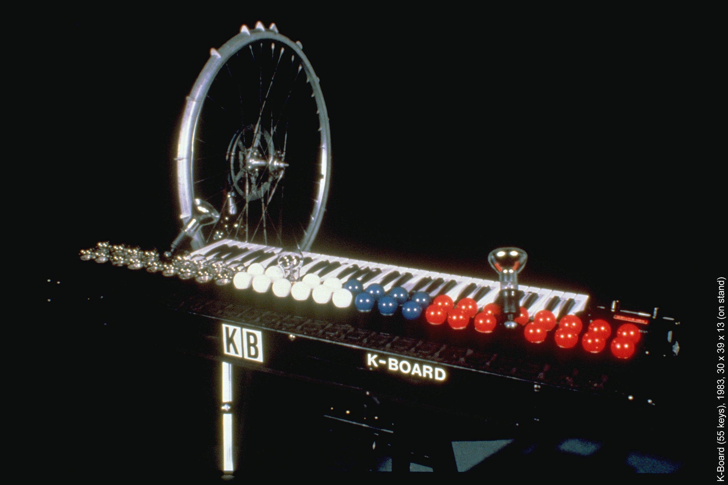 """'K-Board'  (55 keys), 1983, 30 x 39 x 13 (on stand). The K-Board was fashioned from a 55-key organ keyboard with micro switches mounted under the keys which control 55 AC electrical plugs in front of the keys. Each key turns on whatever is plugged into the corresponding outlet. I put a single string directly under the keys lengthwise which is """"fretted"""" or stopped by a small rubber foot on each key. An auto-strum wheel with picks strums the amplified string generating a continuous rhythm, and keys play bass-like microtonal melodies along with light images when pressed."""