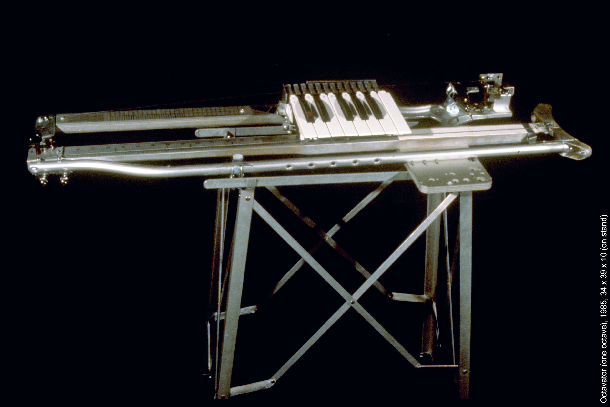'Octavator'  (one octave), 1985, 34 x 39 x 10 (on stand). The Octavator uses one octave of keys with micro switches connected via telephone wires directly to the lamp inputs of six Carousel slide projectors that are aimed to the same area of the screen. Four keys trigger sequences of four slides that can be played live in any order. A master key advances all four slide projectors for the next group of four animated slides. The body of the Octavator is made from an aluminum crutch, a pneumatic door-closing mechanism, a shoe-size guide, ruler, and miscellaneous hardware in addition to the keyboard, It has four strings, two of which are fretted by the keyboard and/or plucking and bowing and is amplified with contact mics.'
