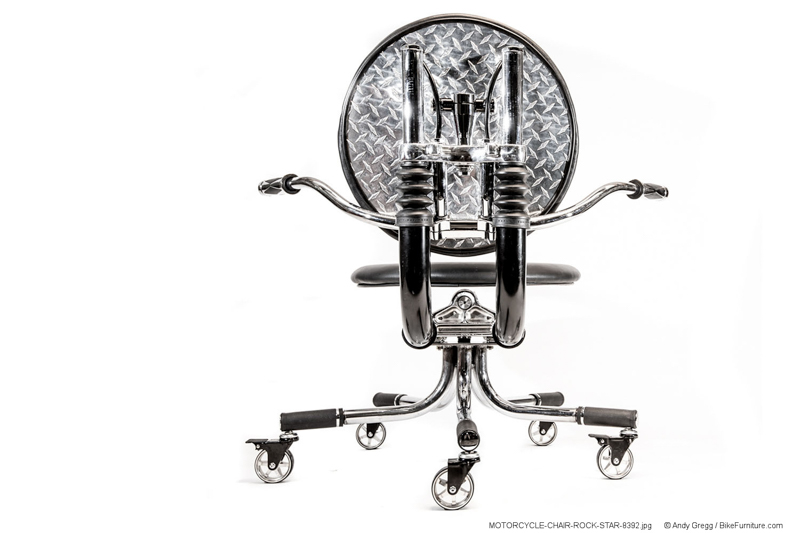 This shows a back view of a chair that uses polished aluminum diamond plate cushion backing, and the use of those black rubber fork boots. Note that the chrome tubes on chairs made in the future would not extend as far as the ones on this chair.