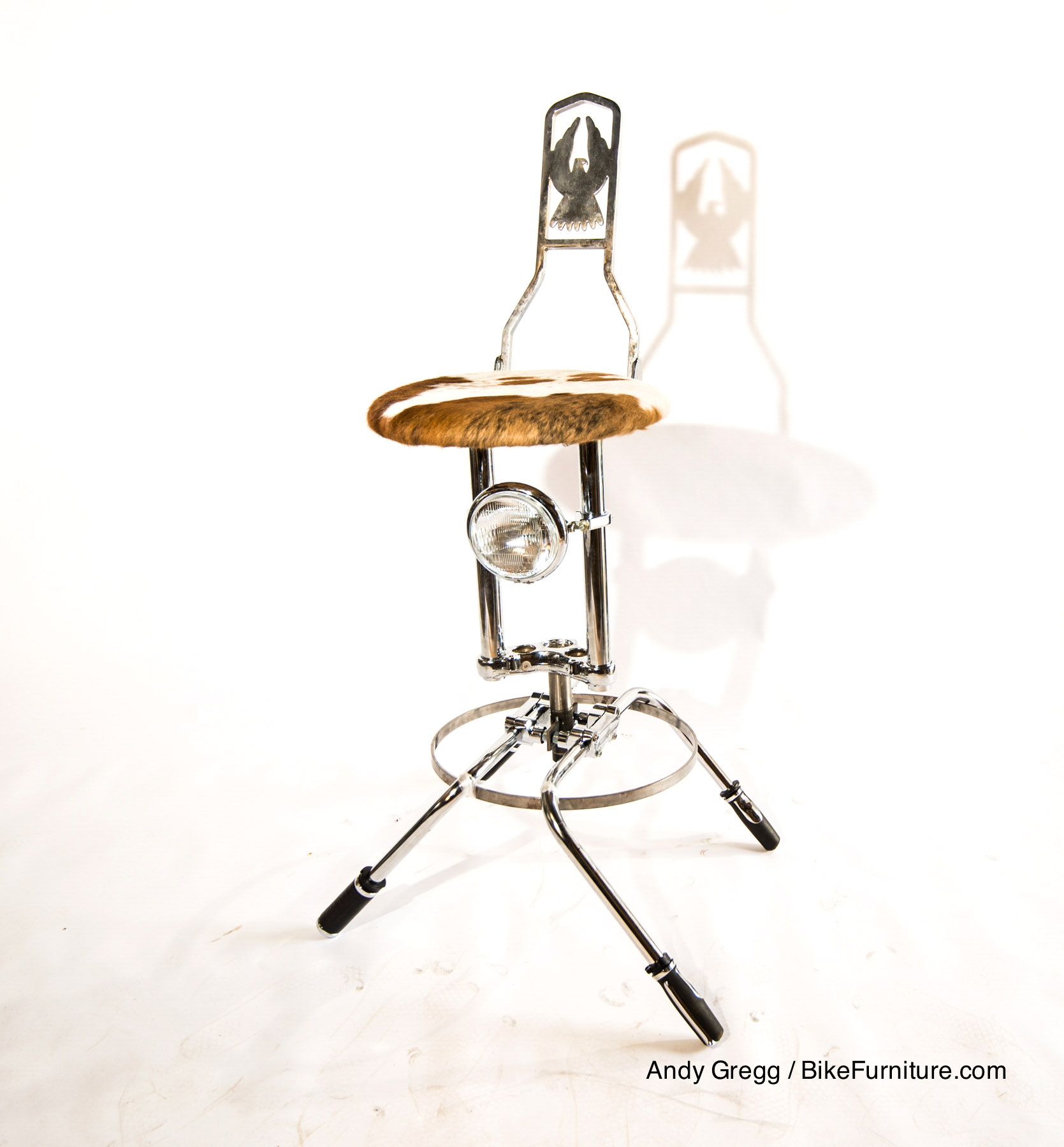Moto bar stool with an actual motorcycle sissybar as a back rest. There are many styles, including padded. Imagine shorter, with an actual motorcycle seat, and without foot ring