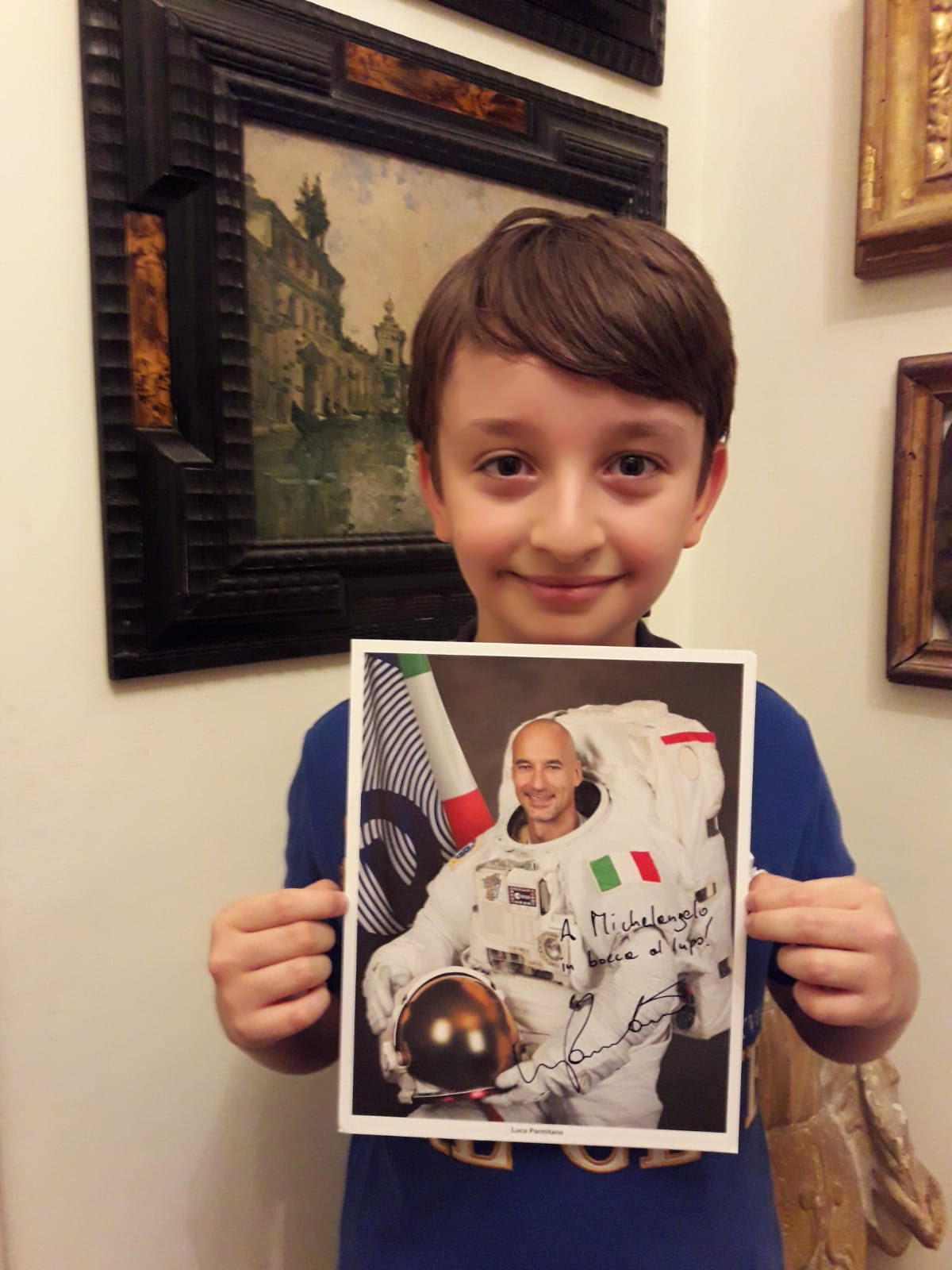 Michelangelo Cambiaghi, at home in Rome, holding his prized autographed photo of Italian astronaut Luca Parmitano.
