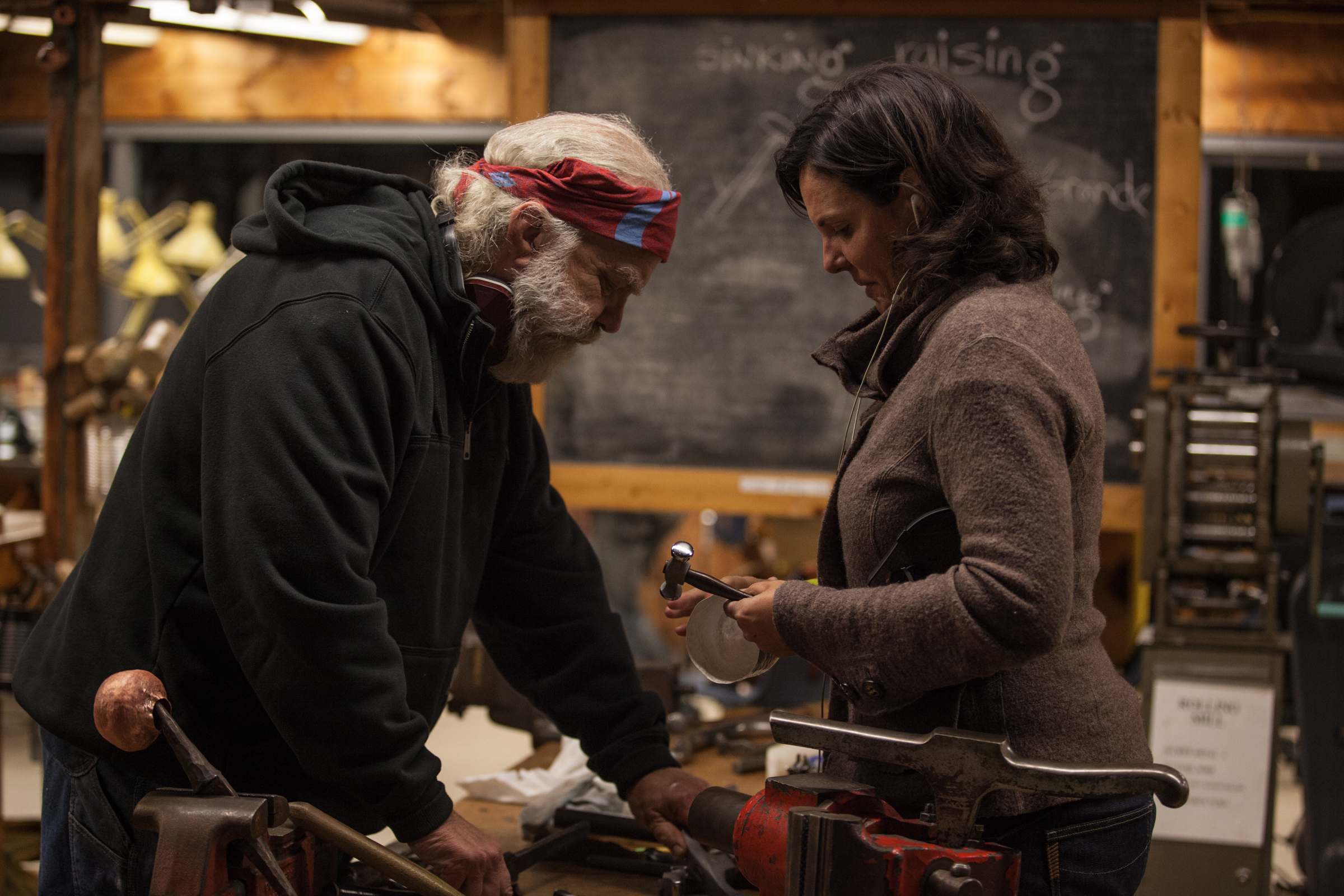 Greg Wilbur  engaging with  Ann Stafford  in the metal shop. Two truly special humans.