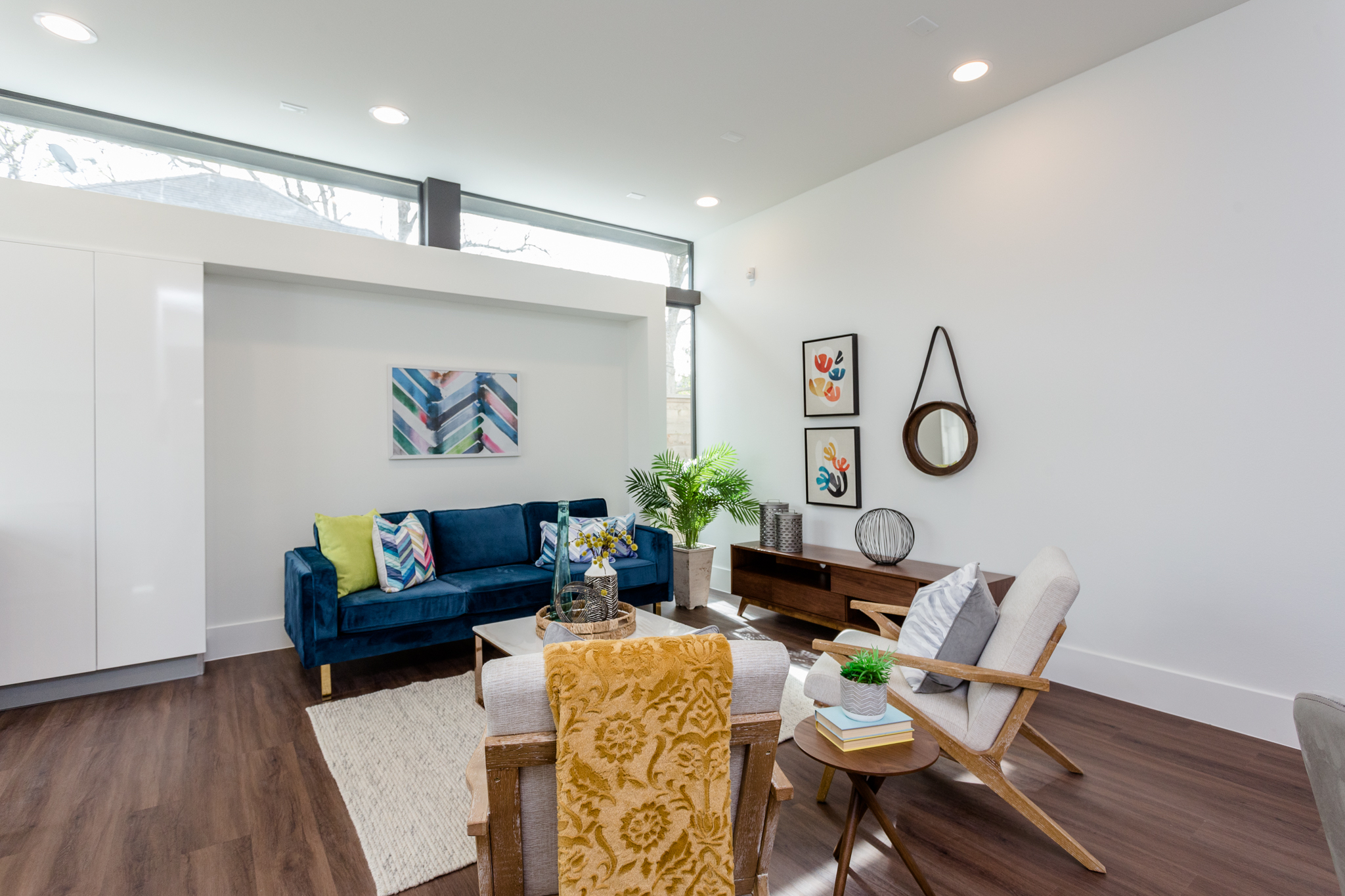 The thoughtfully designed first-floor living area features an elegant recess perfect for audiovisual equipment and carefully positioned clerestory windows that take advantage of 10' ceilings to maximize both wall space and natural light.
