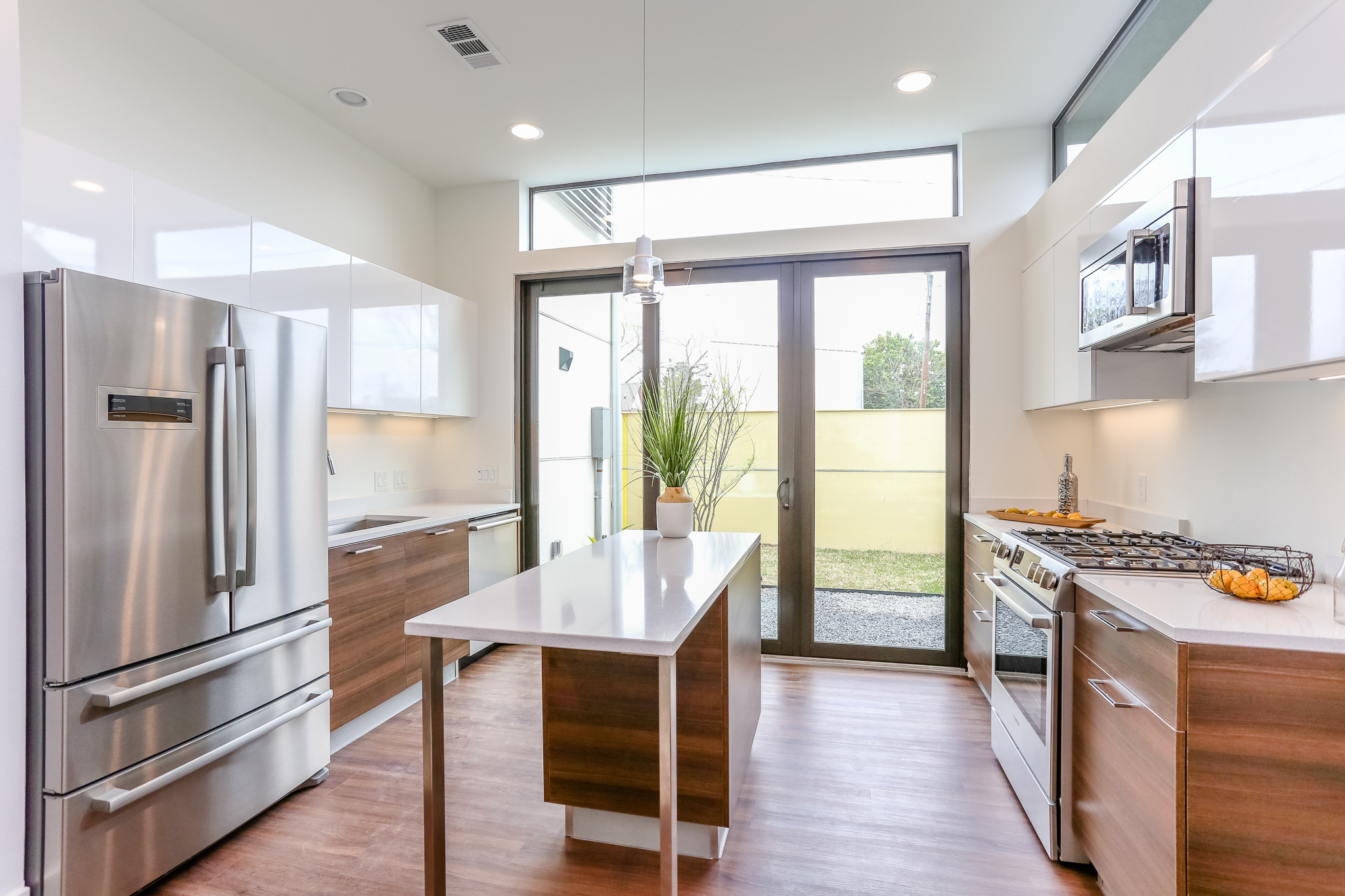 A beautifully appointed kitchen with sleek European style cabinetry, gleaming Silestone countertops, and stainless steel appliances opens onto an adjacent garden.