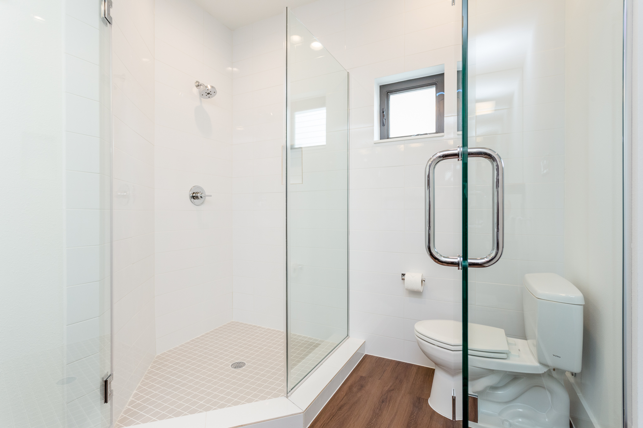 A frameless glass enclosure separates the shower from the water closet. Glass will be frosted to allow for enhanced privacy.
