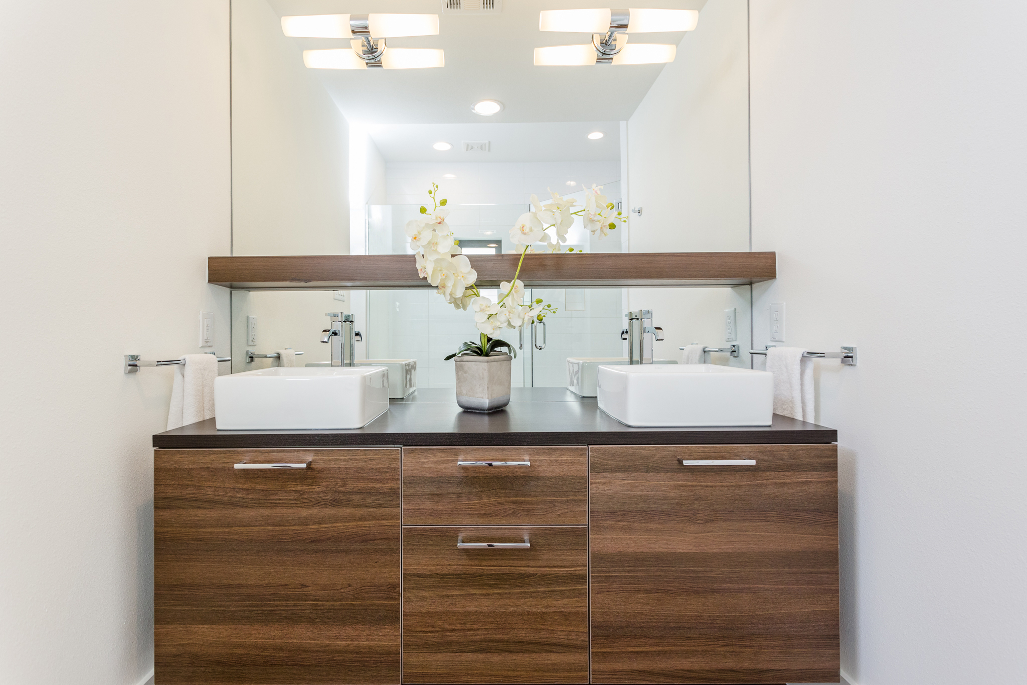 The sleek, floating cabinet and large, sparkling mirror bring a sense of sophistication and openness to the bathroom.