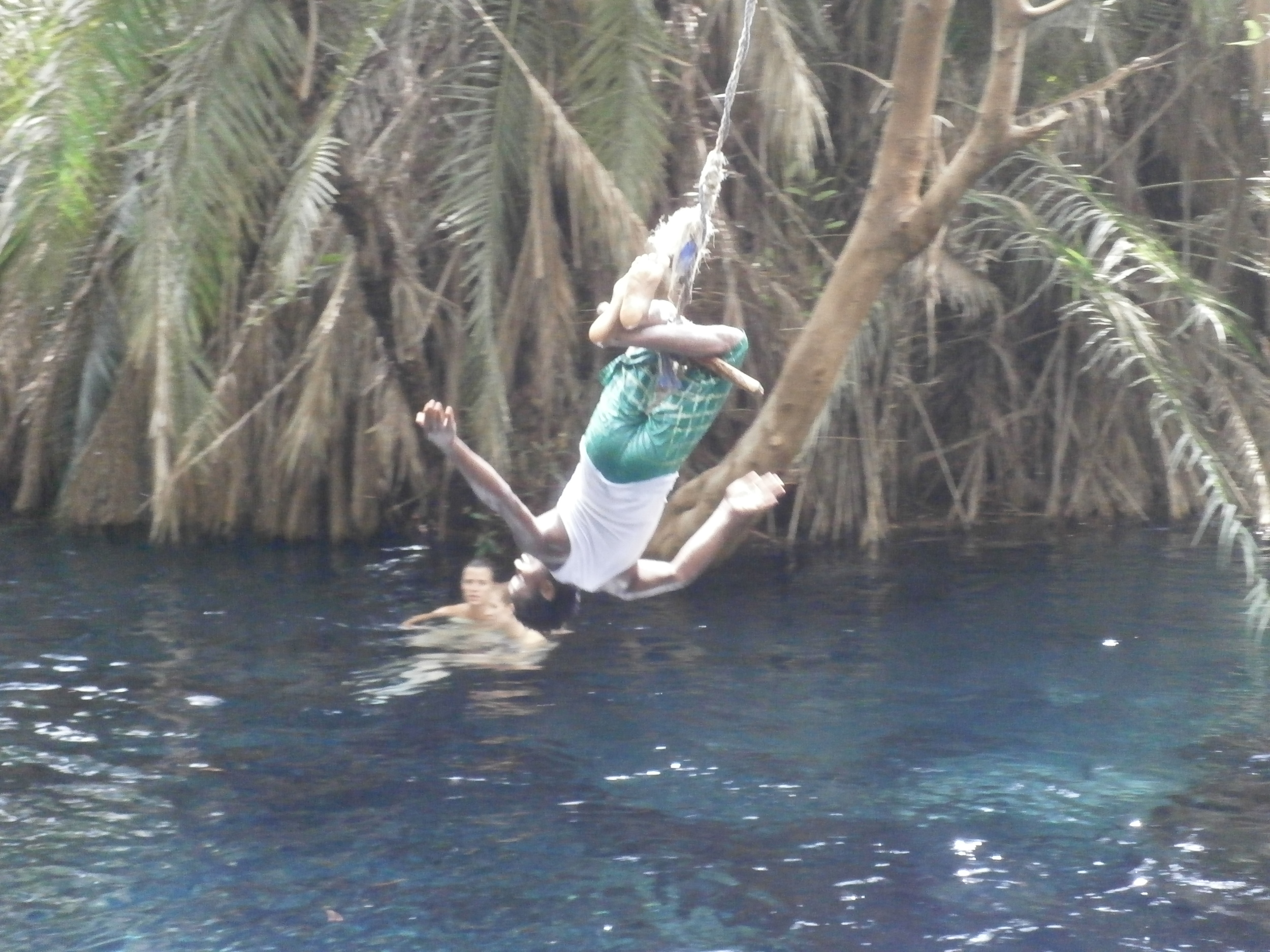 SAM OUR MANAGER OF THE BOYS HOME THRILLS THE GROUP WITH HIS AMAZING GYMNASTIC SKILLS BEFORE PLUNGING INTO THE WATER.