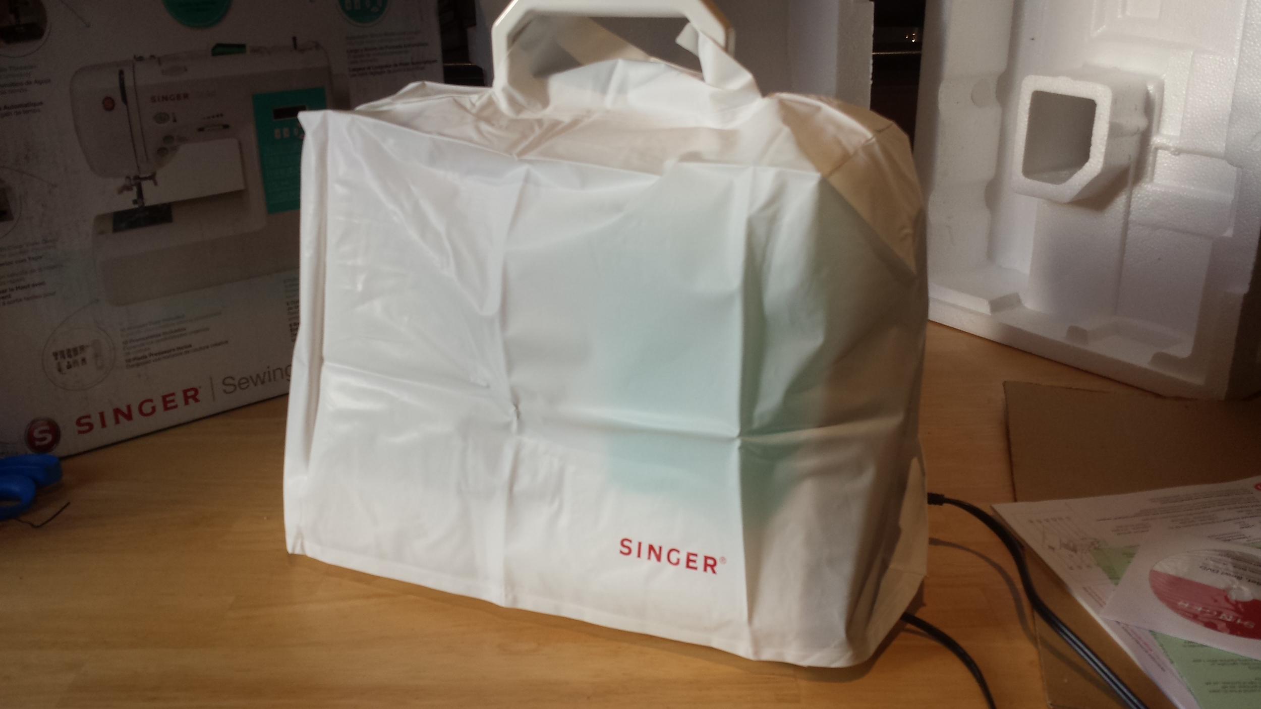 Singer 7258 sewing machine in its vinyl dust cover