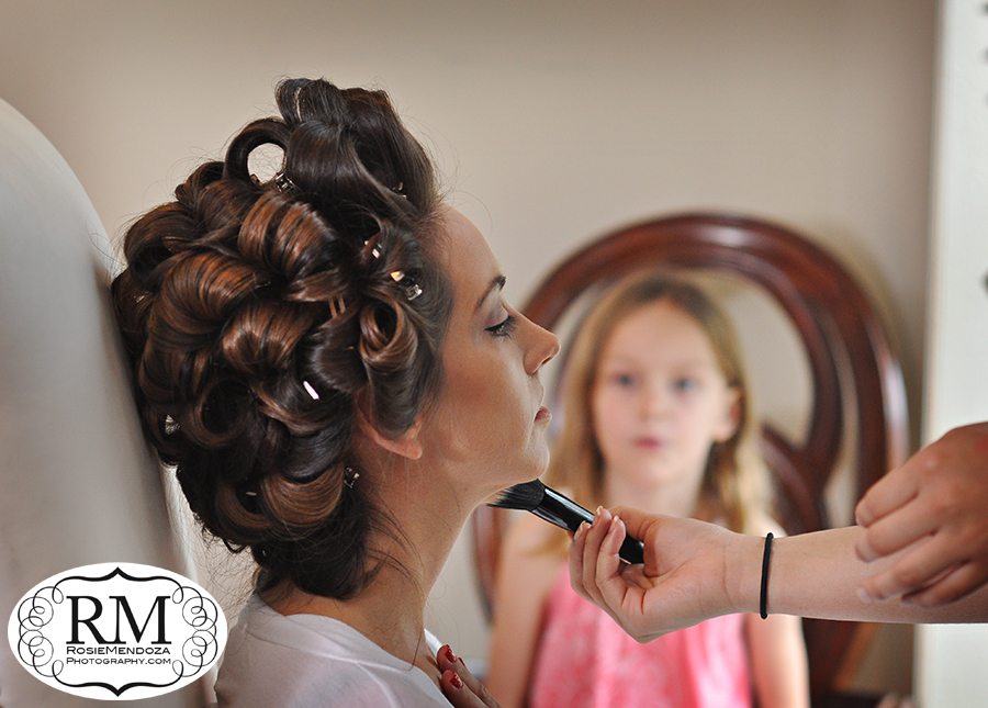 Flower girl loving bride's hair and makeup session