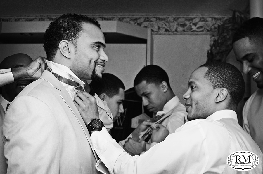 Groomsmen having some fun and helping the groom with tie and such
