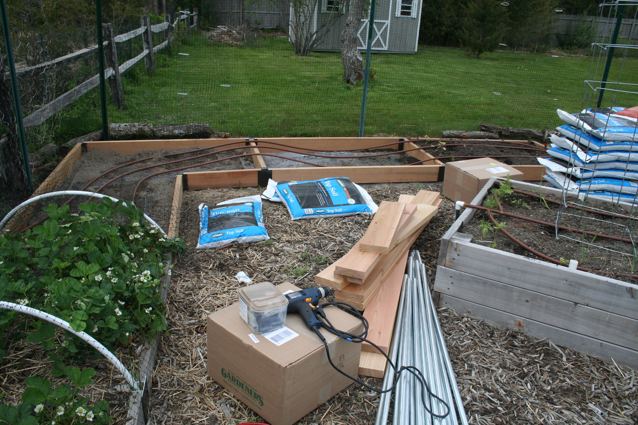Original raised bed on the right; expansion materials and new bed half completed at center.