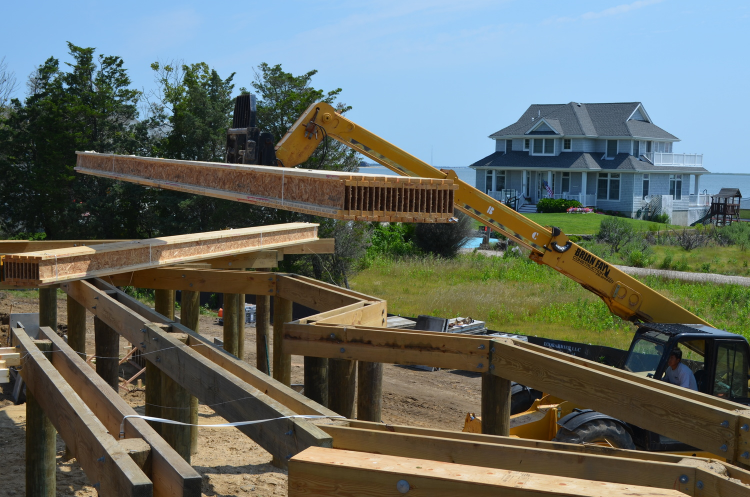 Floor joists being hoisted onto Sunset Green Home's pilings