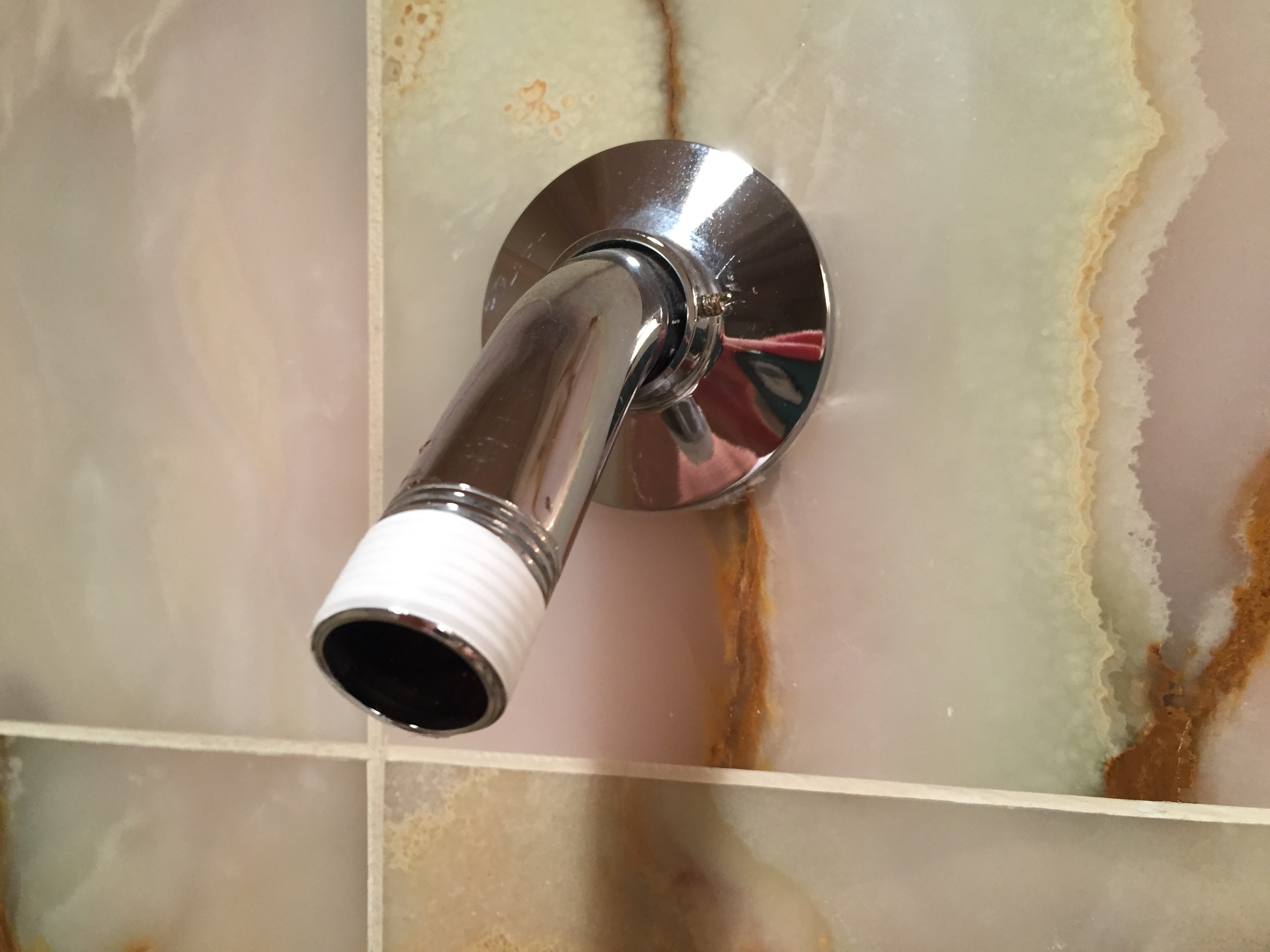 Cut the end of the plumber's tape, which adheres automatically to the pipe threads