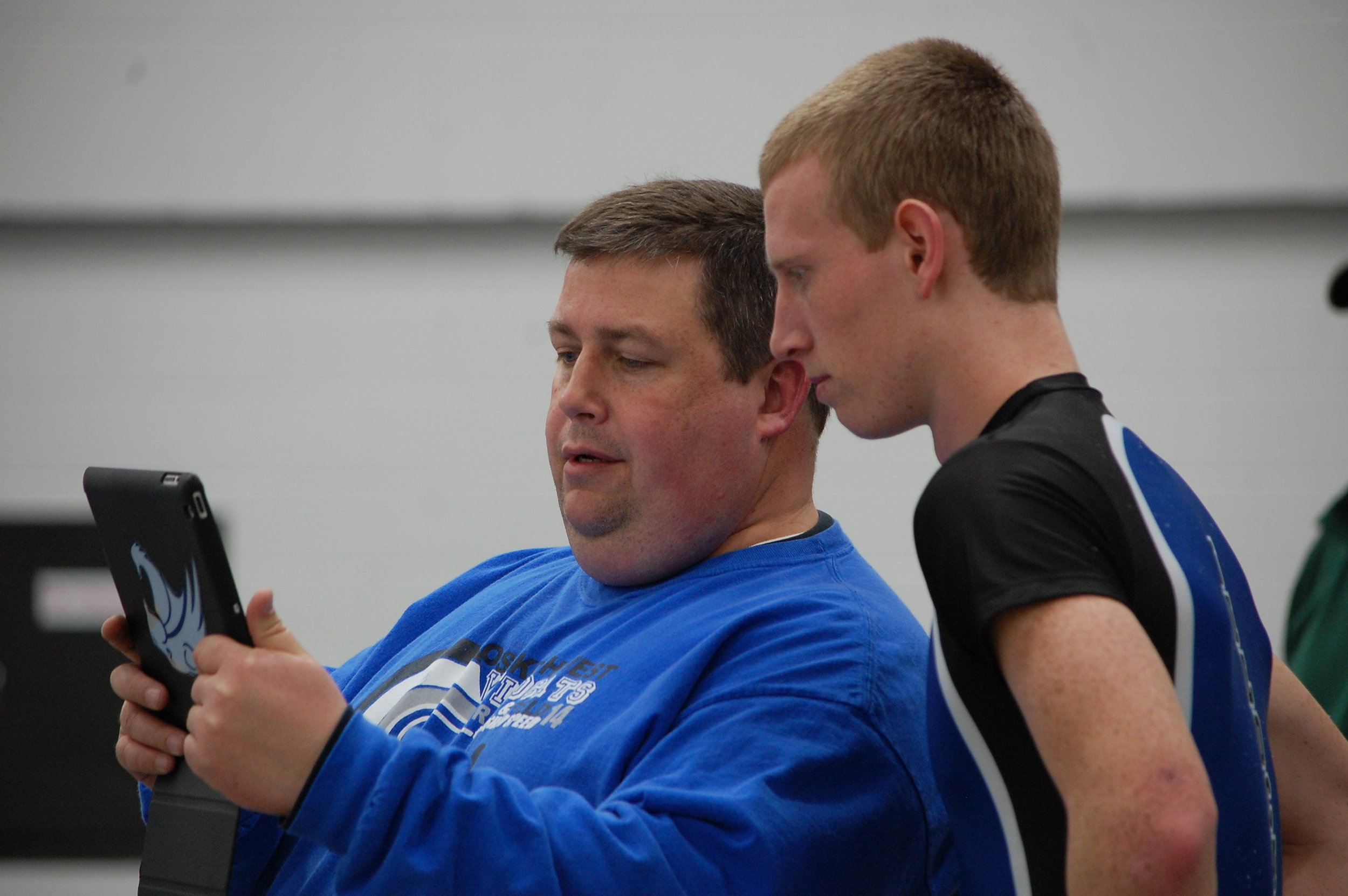 Head coach James Dean shows Joe Vils a video of his high jump in order to better his technique.