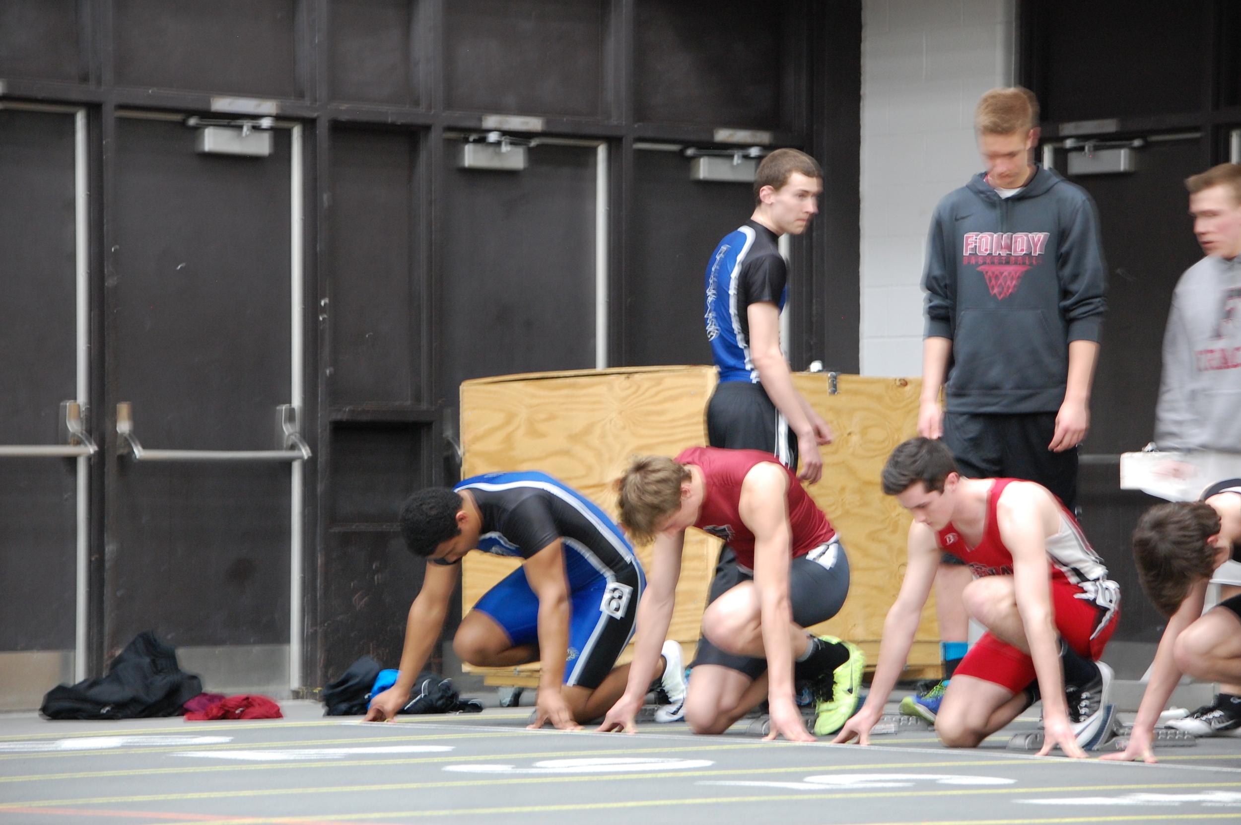 Deshawn Dickinson gets set in his blocks for the 60 meter hurdle finals.