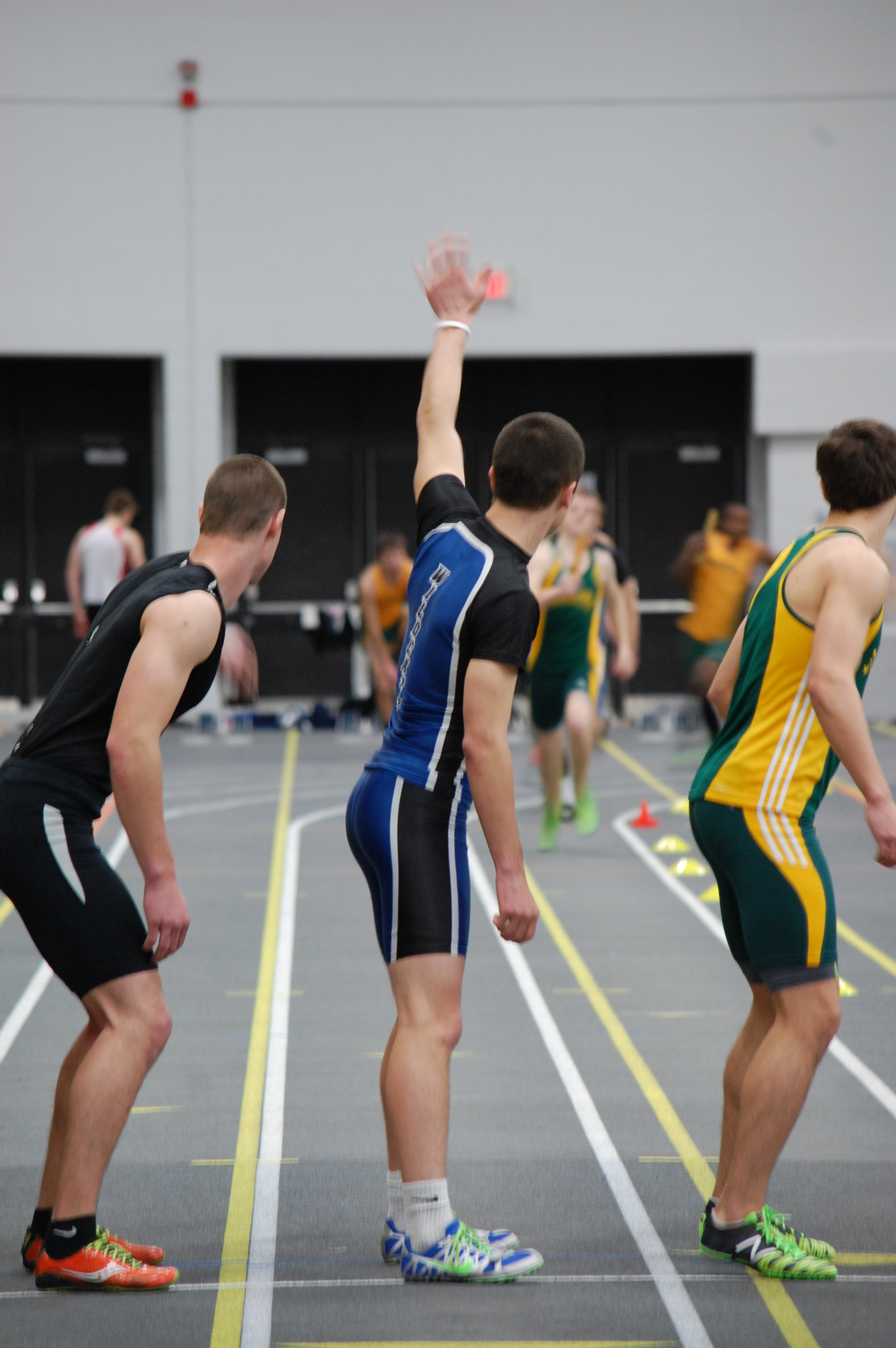 Isaiah Merrill signalsConner Arneson as he prepares to take the baton in the 1600 meter relay.