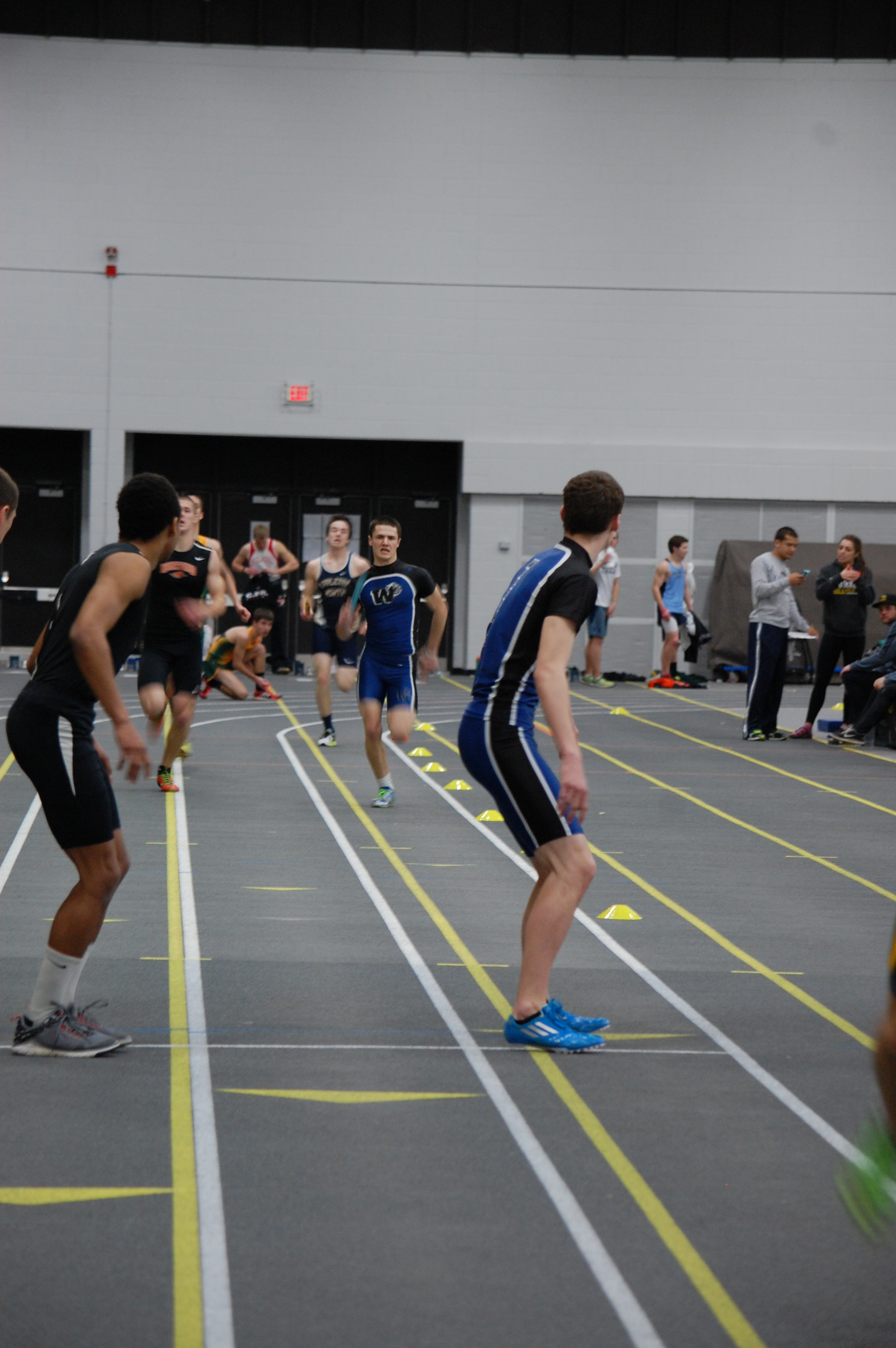 Isaiah Merrill finishes his leg of the 1600 meter relay as he prepares to hand off to Alec Mueller.