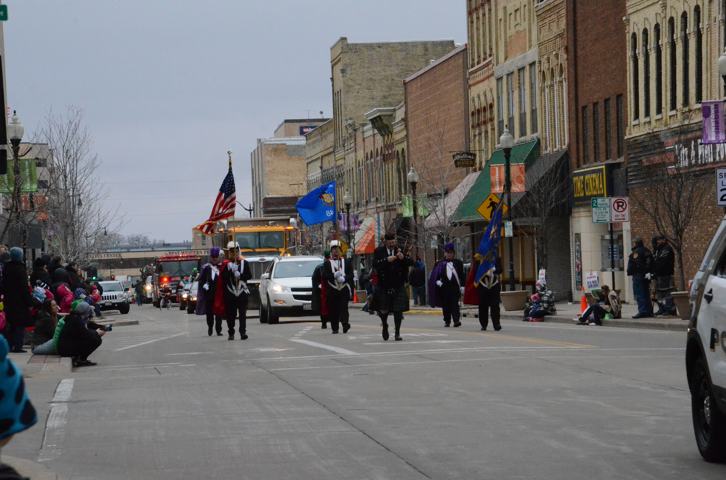 he parade begins with the the sound of bagpipes and the carrying of the Wisconsin flag and United States flag.