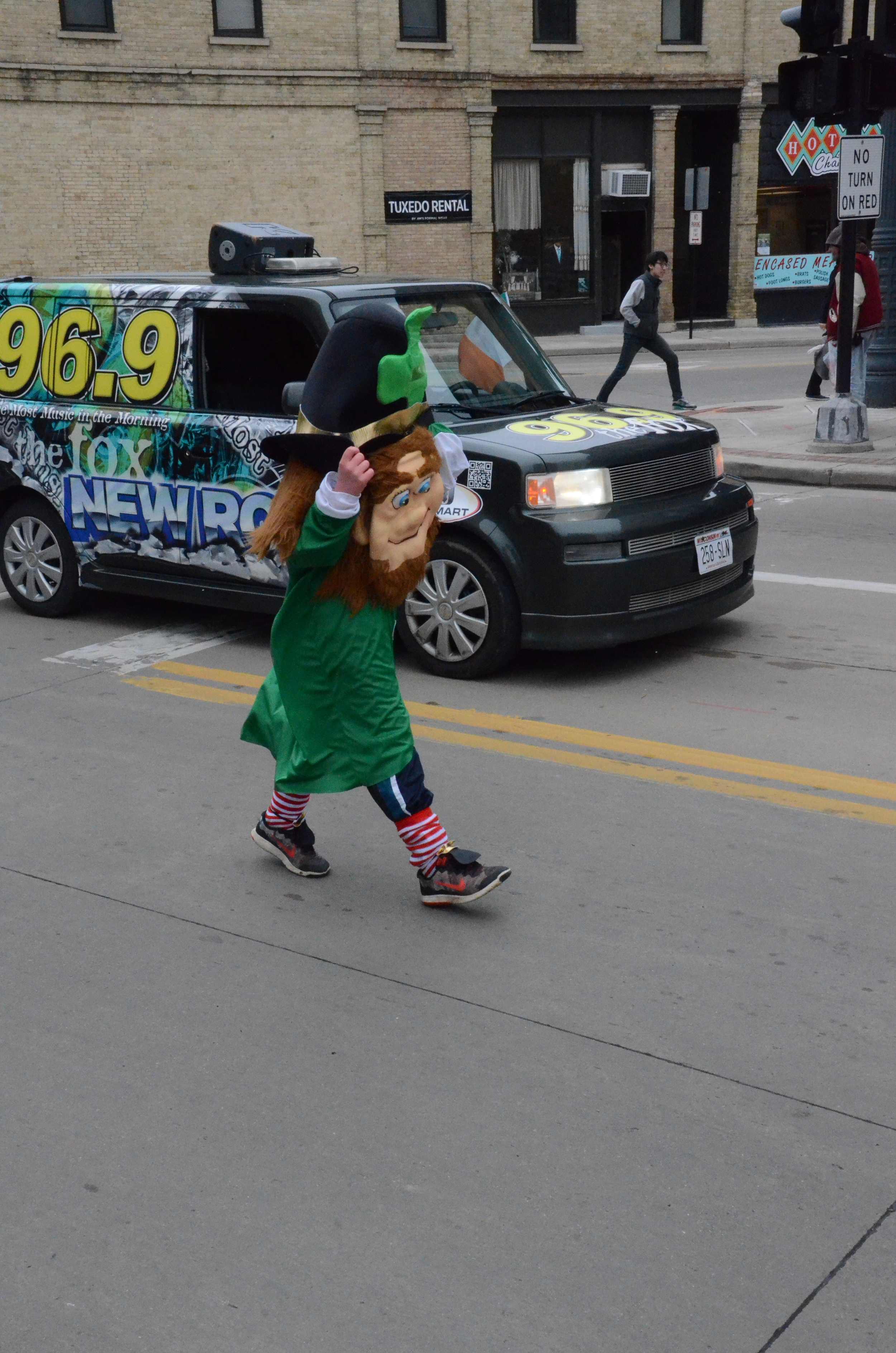 leprechaun spreads St. Patrick's Day cheer during the parade accompanied by the 95.9 The Fox radio station vehicle.