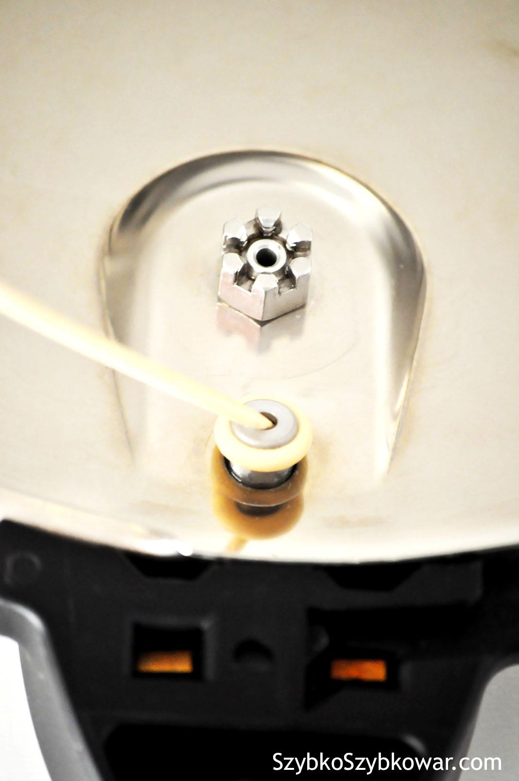Sprawdzanie wylotu blokady pokrywki. W środku jest metalowa kulka, którą należy nacisnąć.