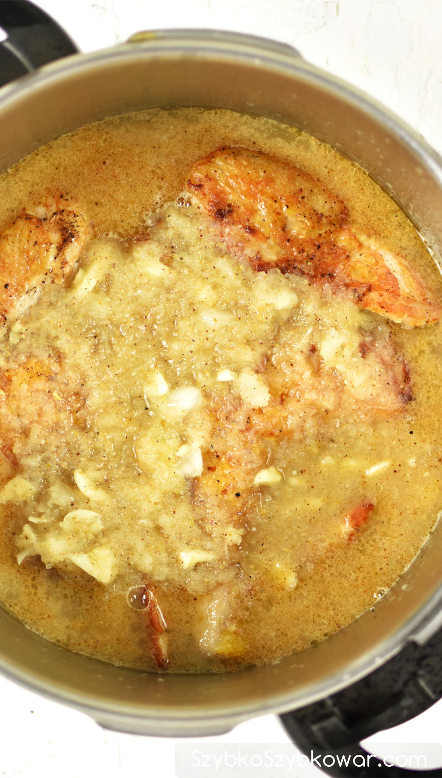 Kurczak zalany bulionem przed gotowaniem.