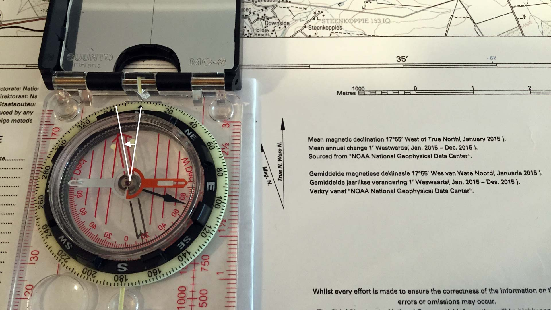 This image shows a compass that has been adjusted for the magnetic declination of the map. Notice how the orienteering arrow is at an angle (18º) to the red meridian lines inside the compass housing. This means that when the red needle sits inside the orienteering arrow, the mirror will point True North.  (Click to enlarge)