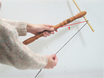 To skein yarn using your niddy noddy, begin by holding the niddy noddy by the center post with your left hand.  Secure the end of the yarn with your left thumb and wrap the yarn over the upper right arm (1).