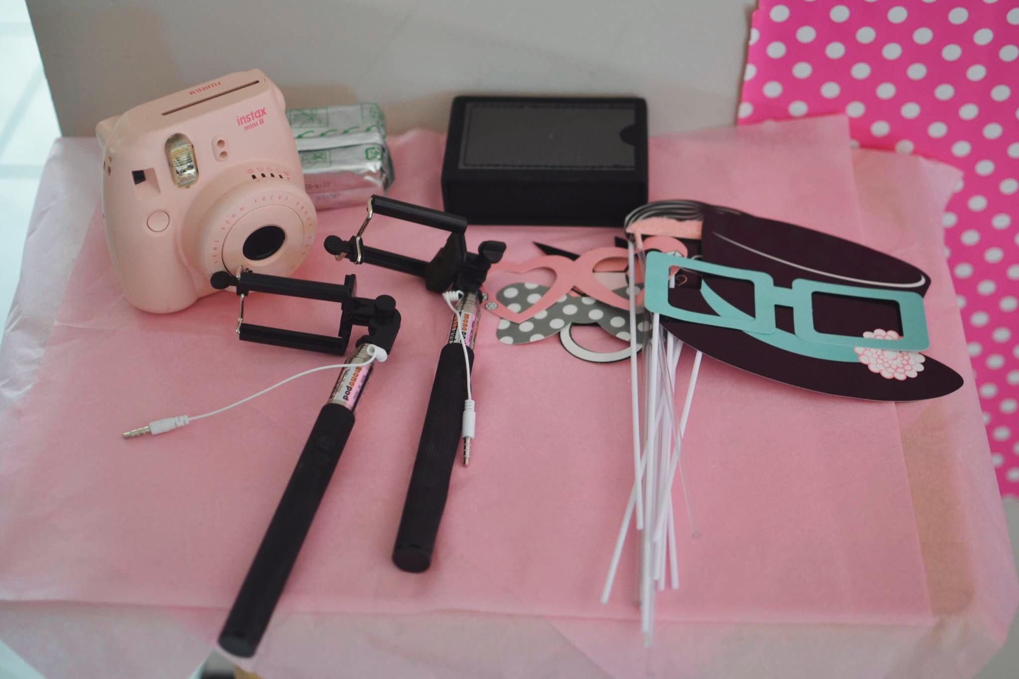 Polaroid camera, selfie sticks, and props