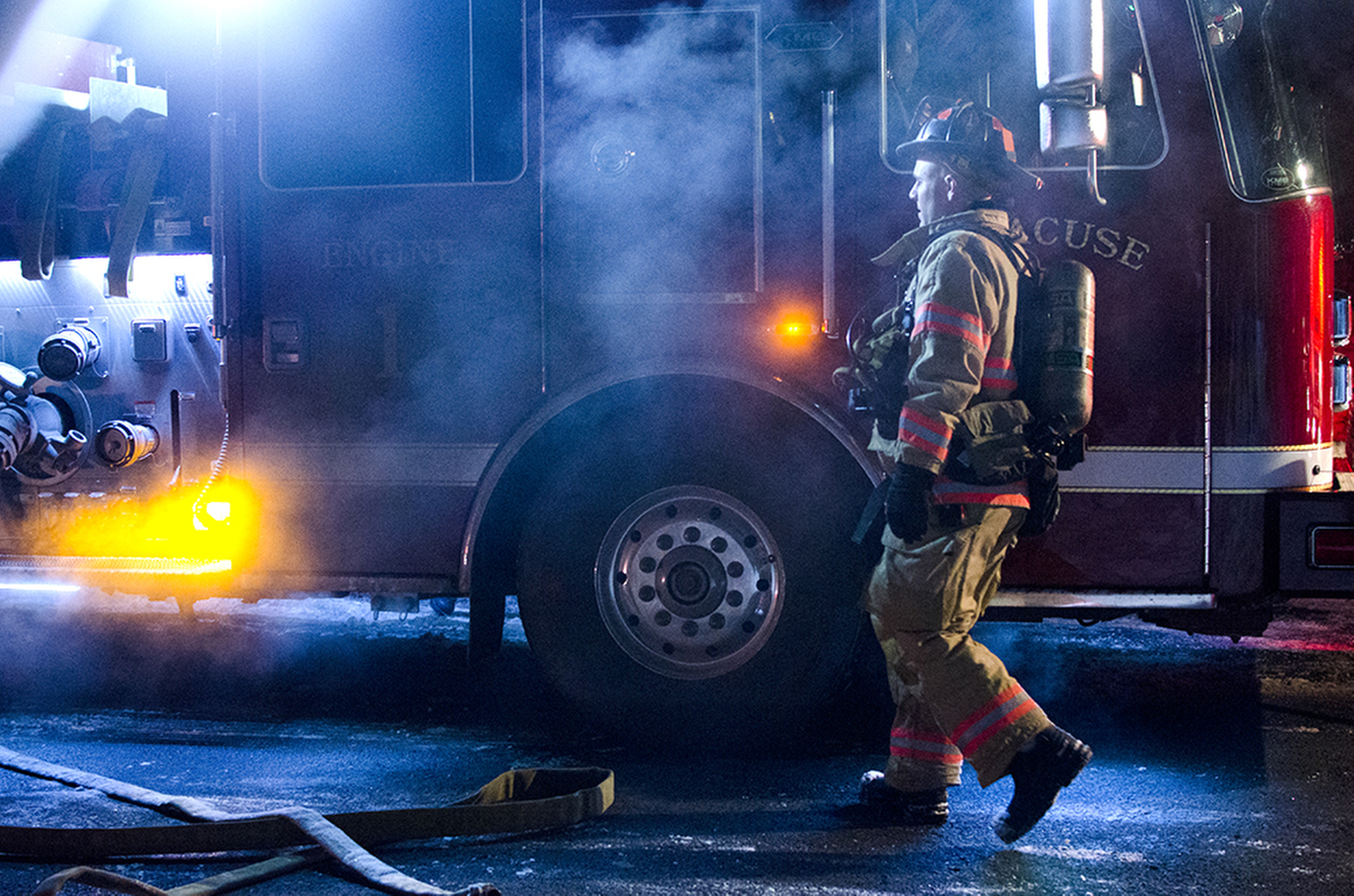 A fire breaks out on the lawn of a Berkeley Dr. resident late Tuesday night in the midst of extreme low temperatures documented at -2° F in Syracuse, NY. Here, a fireman is returning to the truck to coil up hoses and head back to the station.