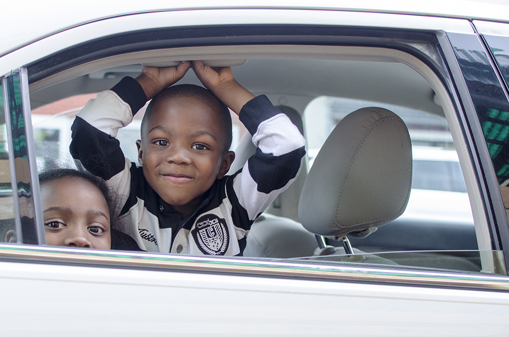 Two children wait in the car as their parents go grocery shopping at an outdoor fresh food shop in downtown Pittsburgh, PA.