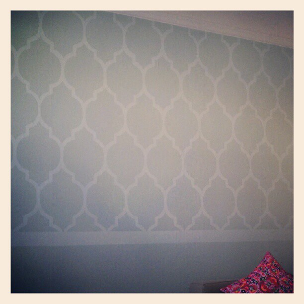 """I recently repainted my walls, and although I really liked having some color, I felt there was something more I could do, and I remember seeing this really cool technique of painting a wallpaper pattern:    http://jonesdesigncompany.com/decorate/painted-wallpaper-a-tutorial/  (you can download a template to use here)    http://littlenannygoat.blogspot.com/2010/09/painted-wallpaper.html    It looked extremely challenging, and I'm always looking for a shortcut and an easy way out, and I think I found some (I'd rather spend more time thinking of ways to make the whole process easier than to actually just doing it the way I'm supposed to).   I had a lot of leftover paint from my wall, so I bought some white paint to mix with the color to create a tonal pattern.    First shortcut:  I made the template shape bigger to have a fewer amount of total shapes to trace/paint. I modified their shape slightly in Illustrator (made it fatter and rounder), printed it out, traced it onto a sturdy shopping bag, and cut it out to use as a template/stencil. It's about 11"""" wide.       I traced this over and over again in pencil onto my wall, and it took HOURS. I messed up once, and erased it…shouldn't have done that because it created a really big smudge on the wall. Luckily after it was painted it got covered up. I tried to leave about ¾"""" space between each shape, and planned on filling those spaces with the paint.       I taped little ¾"""" tabs to the template to use as spacers. I didn't really make any other measurements on the wall, just eyeballed it.       Penciled outlines.    Second shortcut:  the examples on those sites paint INSIDE the traced shape, meaning they get double lines, and essentially have to paint every outline of every shape. I decided to paint OUTSIDE the traced shape (the negative space, per se) so the merged area is what I ended up painting (less shapes to paint).       Me: painting outside of the lines.       Them: painting inside the lines, resulting in two stroke"""