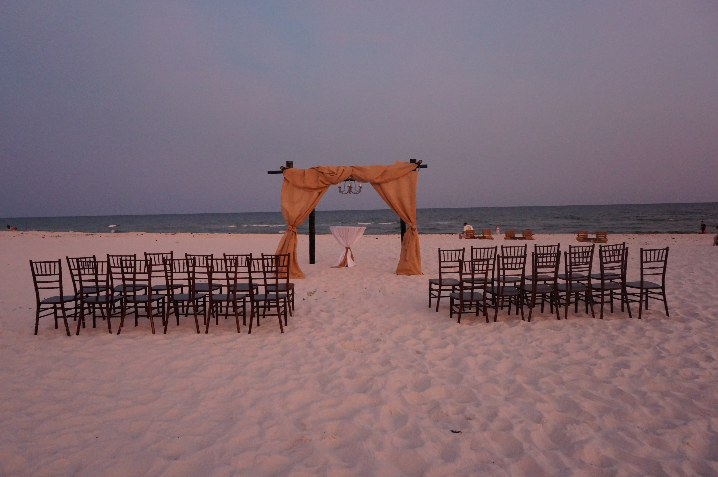 White beach wedding with burlap and dark bamboo arbor