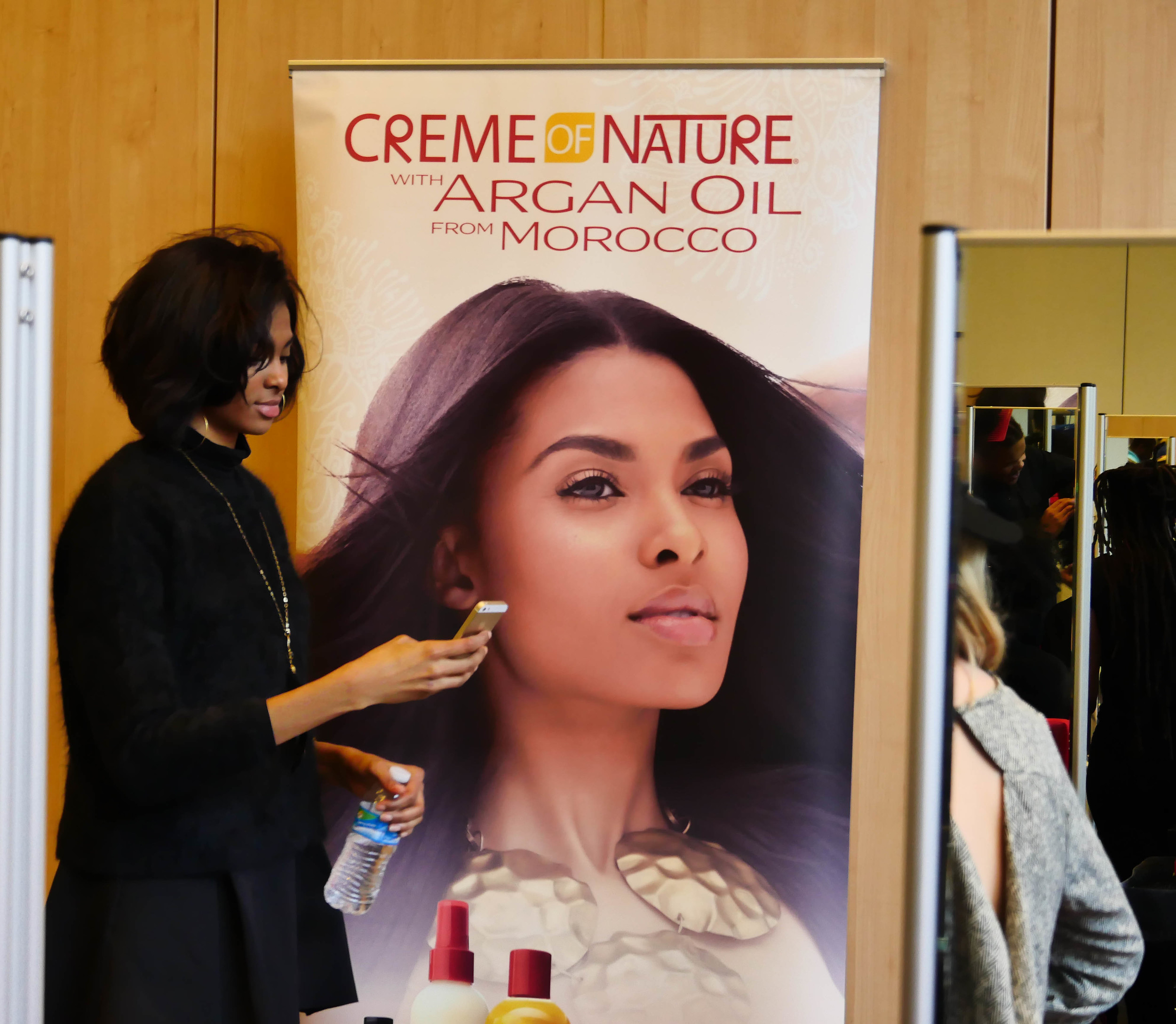 Tierra along side a poster with of the most recent Creme of Nature campaign