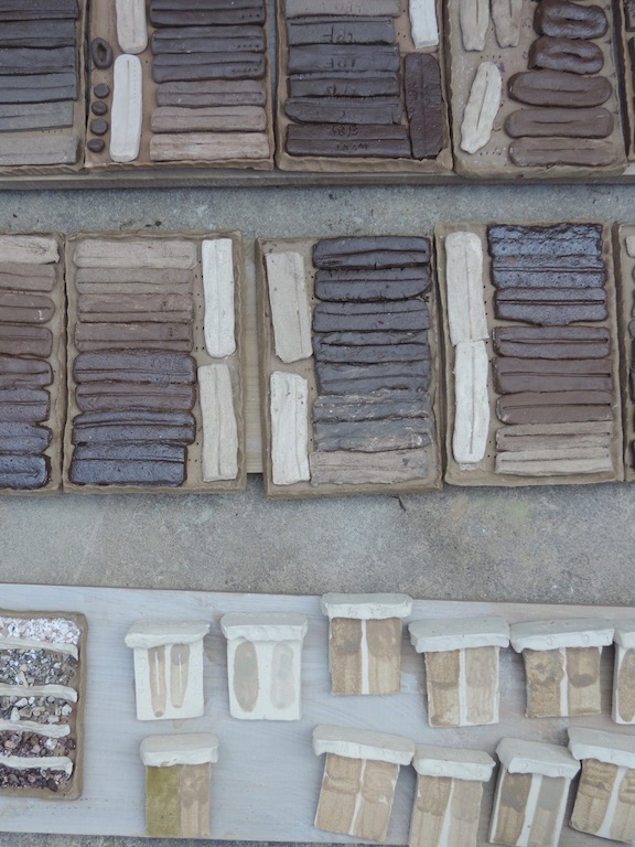Various tests made by participants during the workshop. Upper tiles: line blend tests of two low-firing clays with refractory Bennington kaolin. Lower left: aggregate tests of crushed stones. lower right: vitreous slip tests made from commercial clay with additions of silty clay soil.