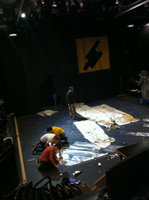 Lighting supervisor teaching the electrics crew how to focus while the painters work on the floor treatment