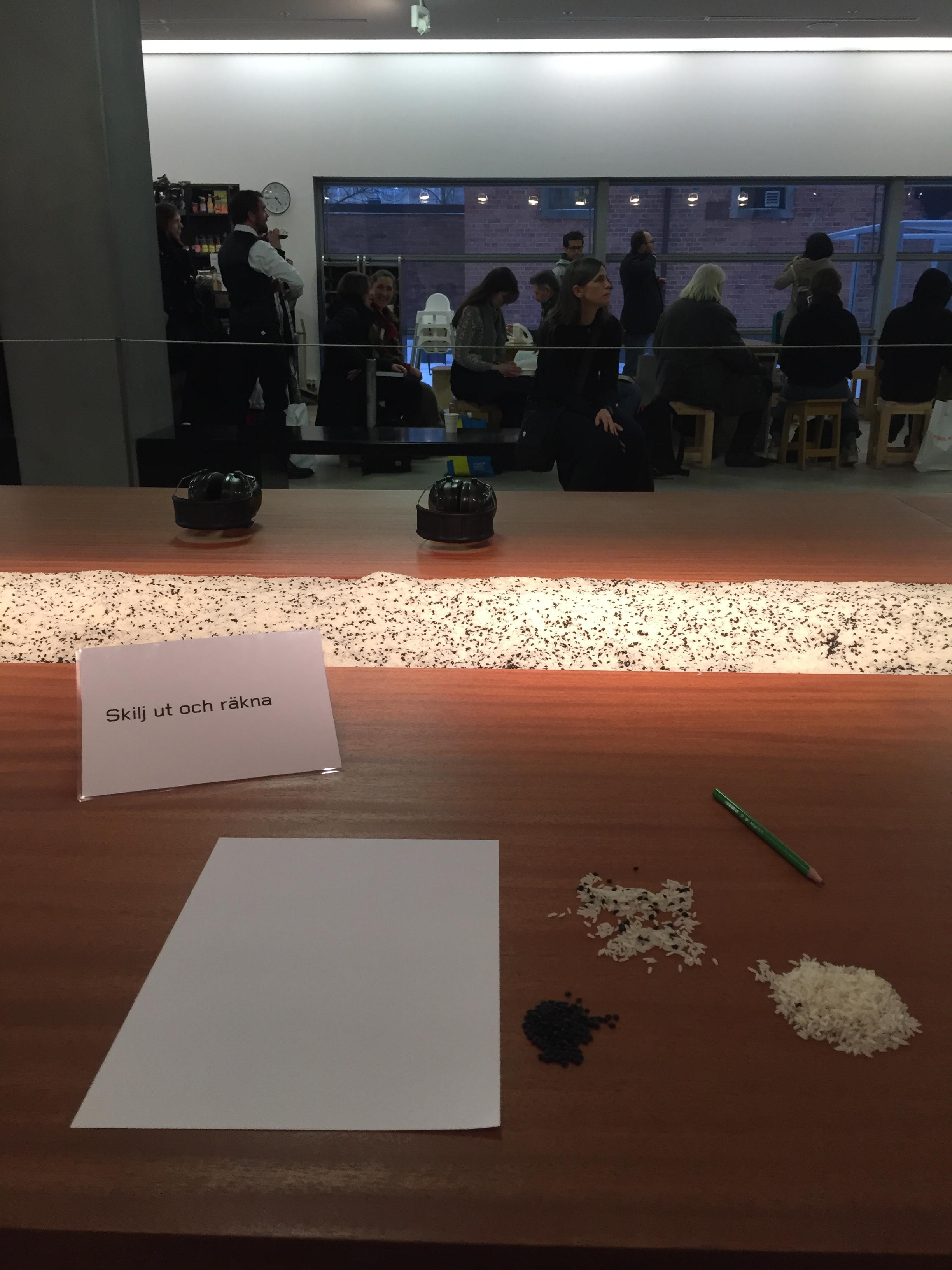 """Counting the Rice, 2015. Övning med publikdeltagande ur en serie workshopar betitlade """"Cleaning the House"""" (1979–). I bakgrunden kön till Marina Abramovics signering av självbiografi och utställningskatalog, Moderna Museet i Stockholm den 8 mars 2017."""