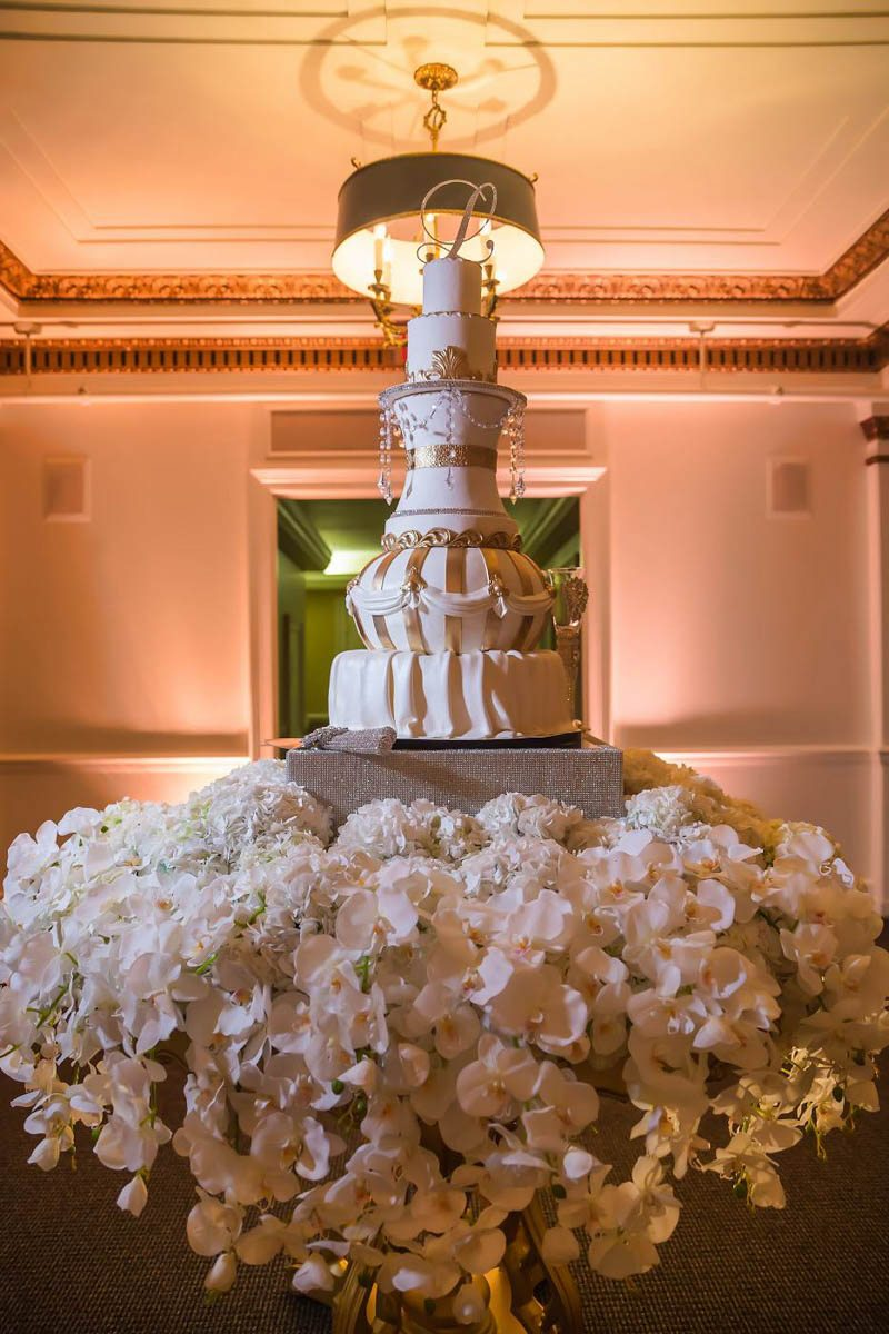 Gold-and-White-Tiered-Cake-with-Jewels-and-white-flowers-.jpg