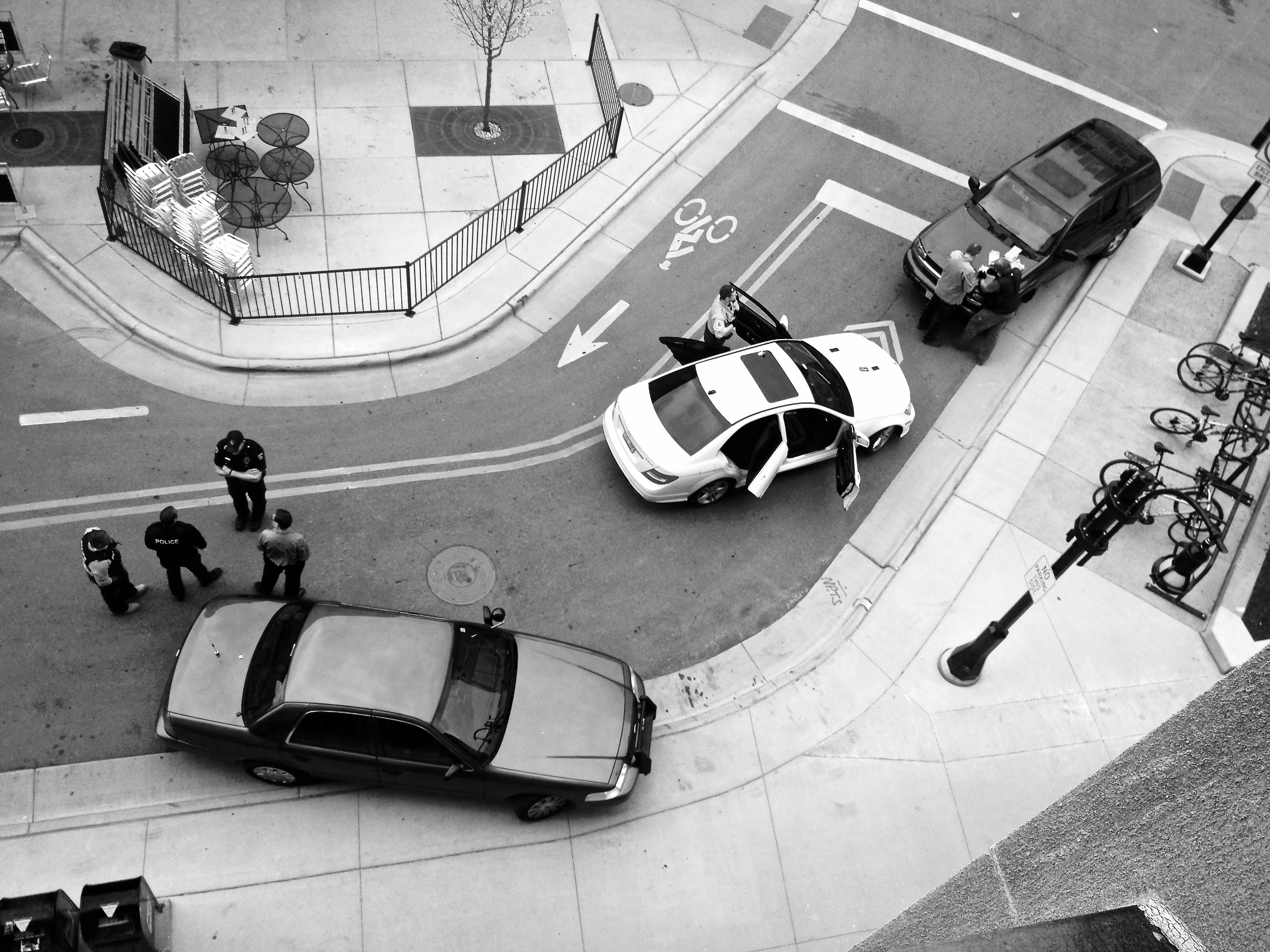 Scene of the Crime (2). Downtown. Madison, Wisconsin. April 2016. Police talk and gather evidence at the scene of an armed traffic stop and arrest.  © William D. Walker