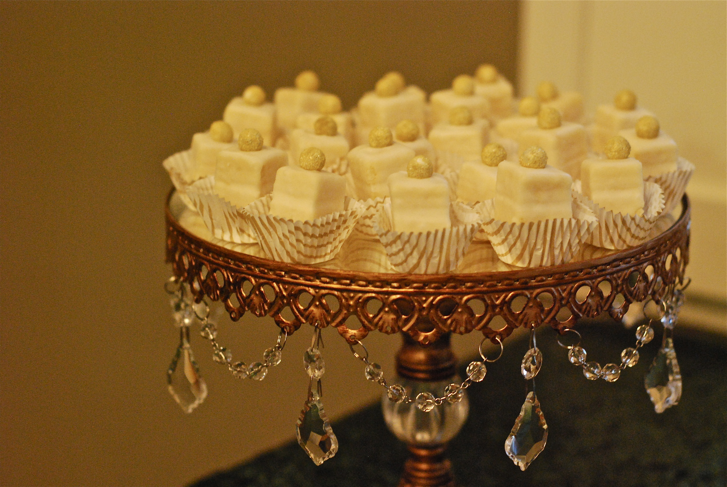 Vanilla petite fours topped with golden sanding sugared chocolate candies.
