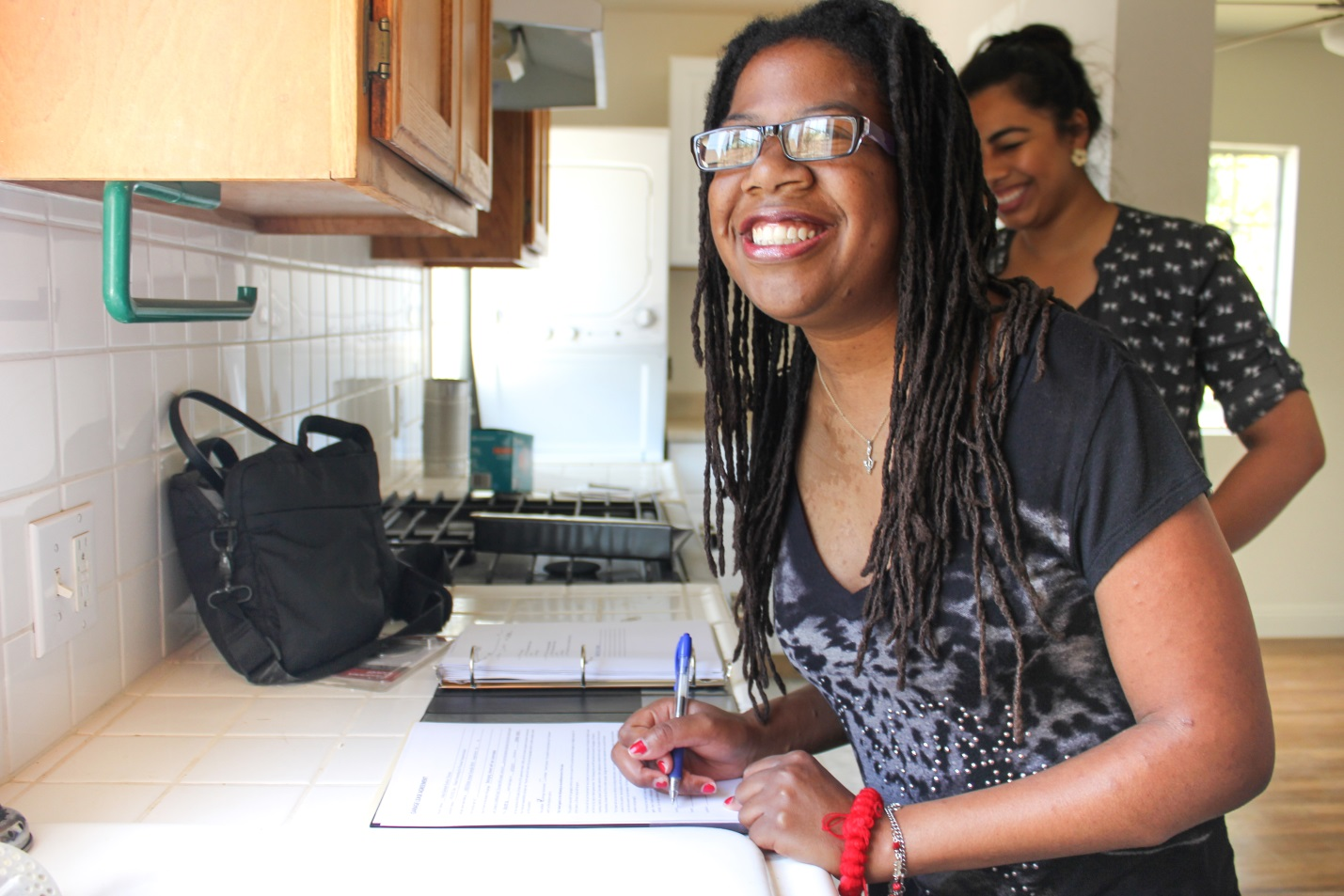 New resident, Asha, signs the lease at her first HOPE Independent Living home. Asha is the 71st person to receive housing as part of HOPE's  80 by 18  goal.