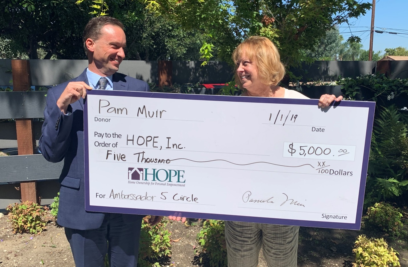 HOPE Executive Director Kristin Martin receives a generous $5,000 donation from Pam Muir as she officially joins the Ambassador 5 Circle. (HOPE)
