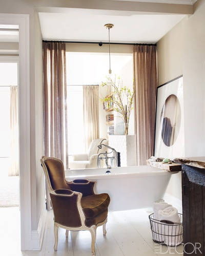 The claw-foot bath was the perfect addition to the couples ensuite bathroom  with the open plan space being divided only by a simple sheer curtain.
