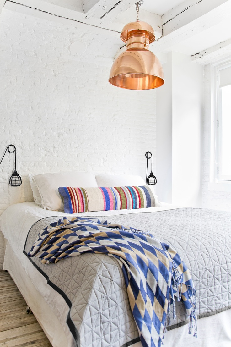 Copper pendant lighting, exposed painted brick wall, textured and patterned bed linen. My favourite.