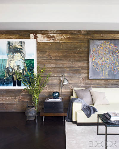 The living room walls are clad with reclaimed barn wood.  Photograph by Jackie Nickerson. Painting by Carlos Vega.