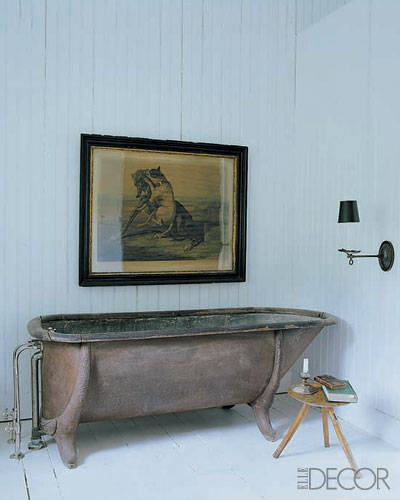 An oak-rimmed galvanized-metal tub, milking stool, and antique print in the master bath.