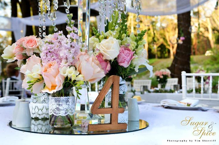 Bright blooms in lace jars placed on a mirror centerpiece with a chrystal candelabra is perfect for this beautiful outdoor wedding. Styled by Sugar & Spice Events.